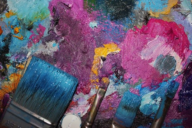 Picture of a color palette and a few paint brushes. The overall tint is pink, purple and blue.