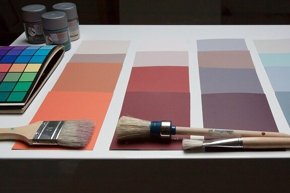 Picture of a color palette, with paint brushes lying on them. In the picture, in the left corner, you can see some paint.