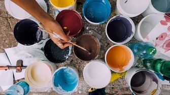 Picture of different buckets with all different types of colors of acrylic paint. You see a hand in the picture, holding a paint brush, reaching out for the brown paint.