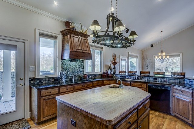 Picture of a kitchen. In the center of the photo you see a kitchen island with a wooden countertop. Around the island you see the rest of the kitchen, with a lot of dark brown cabinets.